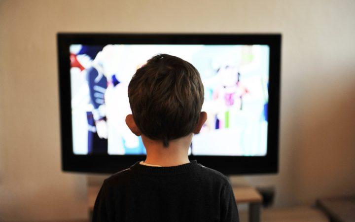 Bir çocuk, gözünü ayırmadan televizyon izliyor.