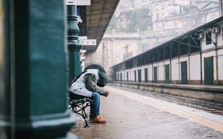 Tren bekleyen karamsar adam.