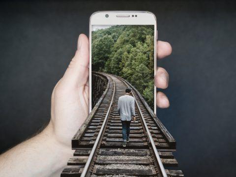 Telefonunda sanal dünyaya yolculuk yapan bir adam.
