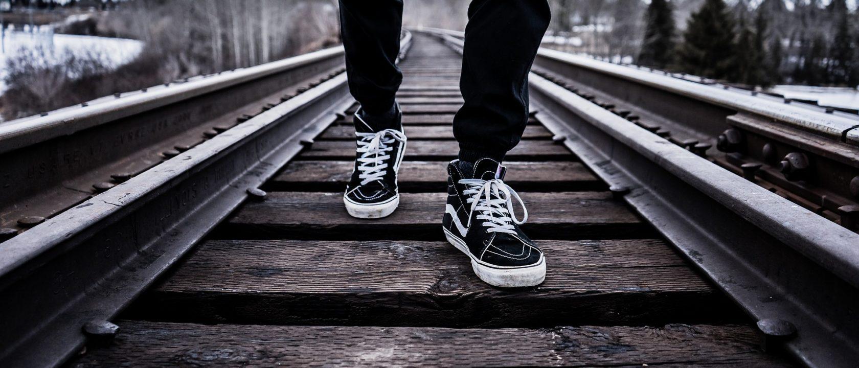 Tren raylarında yürüyen adam.