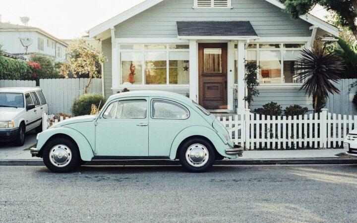 Çok güzel güneşli bir günde bir evin bahçesi, önünde araba park etmiş.