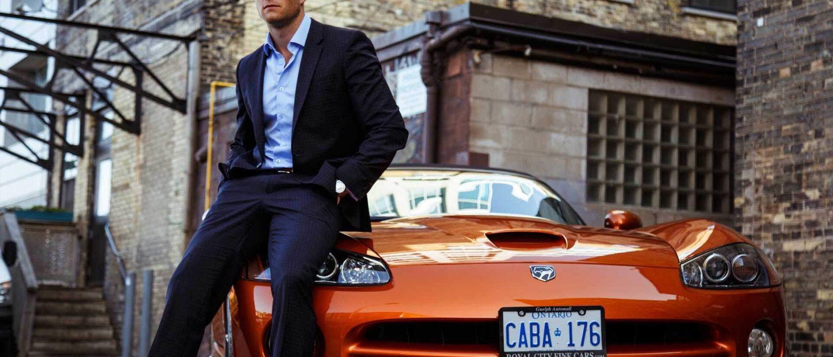 Şık giyimli bir adam turuncu spor arabasının kaputuna oturmuş.