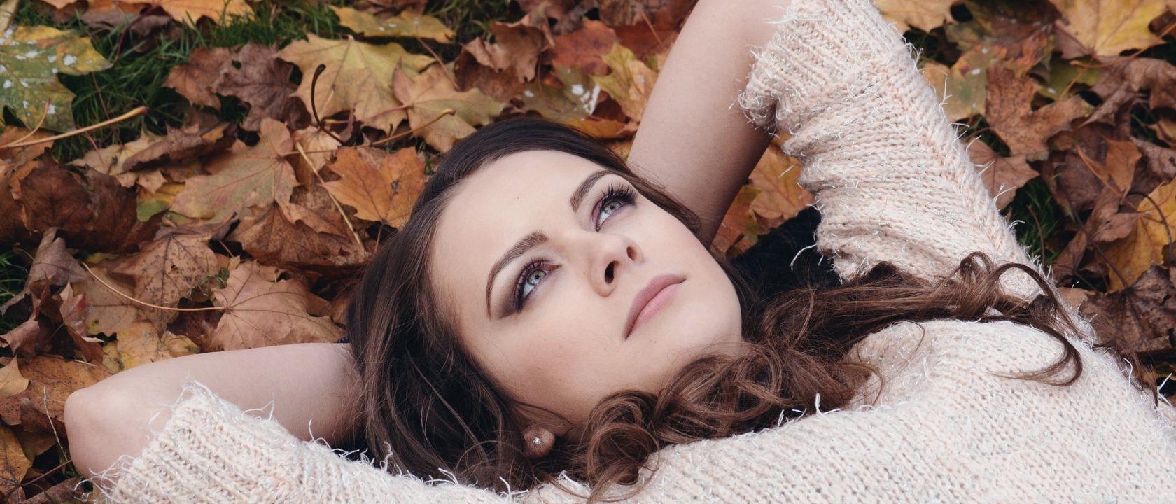 Yaprakların üzerine uzanıp düşünen kadın.