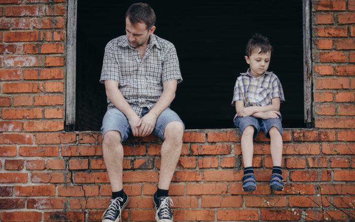 Üzgün adam ve çocuk bir pencerede oturmuş.
