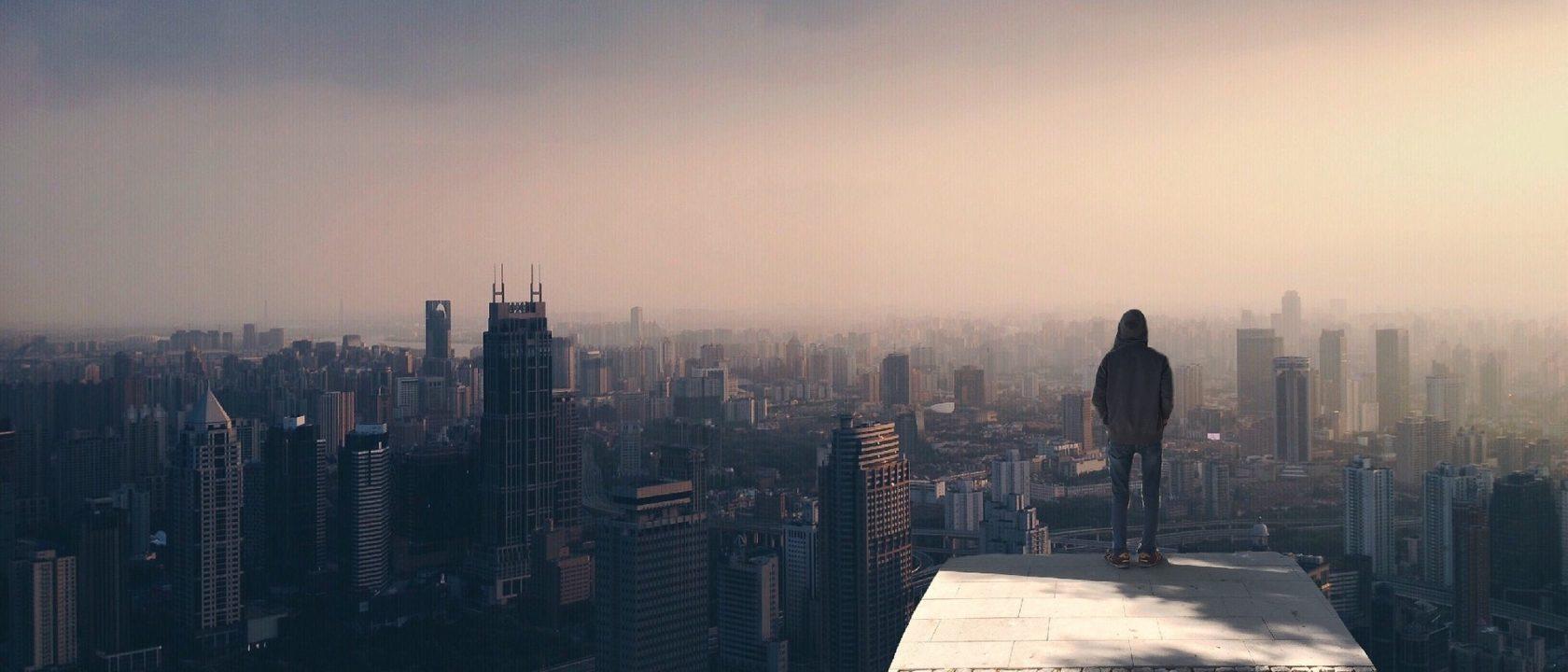Bir adam yüksek bir yerden gökdelenlere bakıyor.