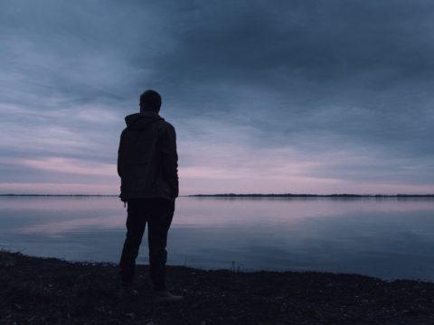 Günbatımında, sahilde duran bir adam.