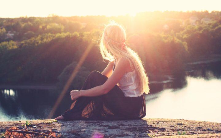 Göl kenarında oturan, gün batımına bakan kadın.