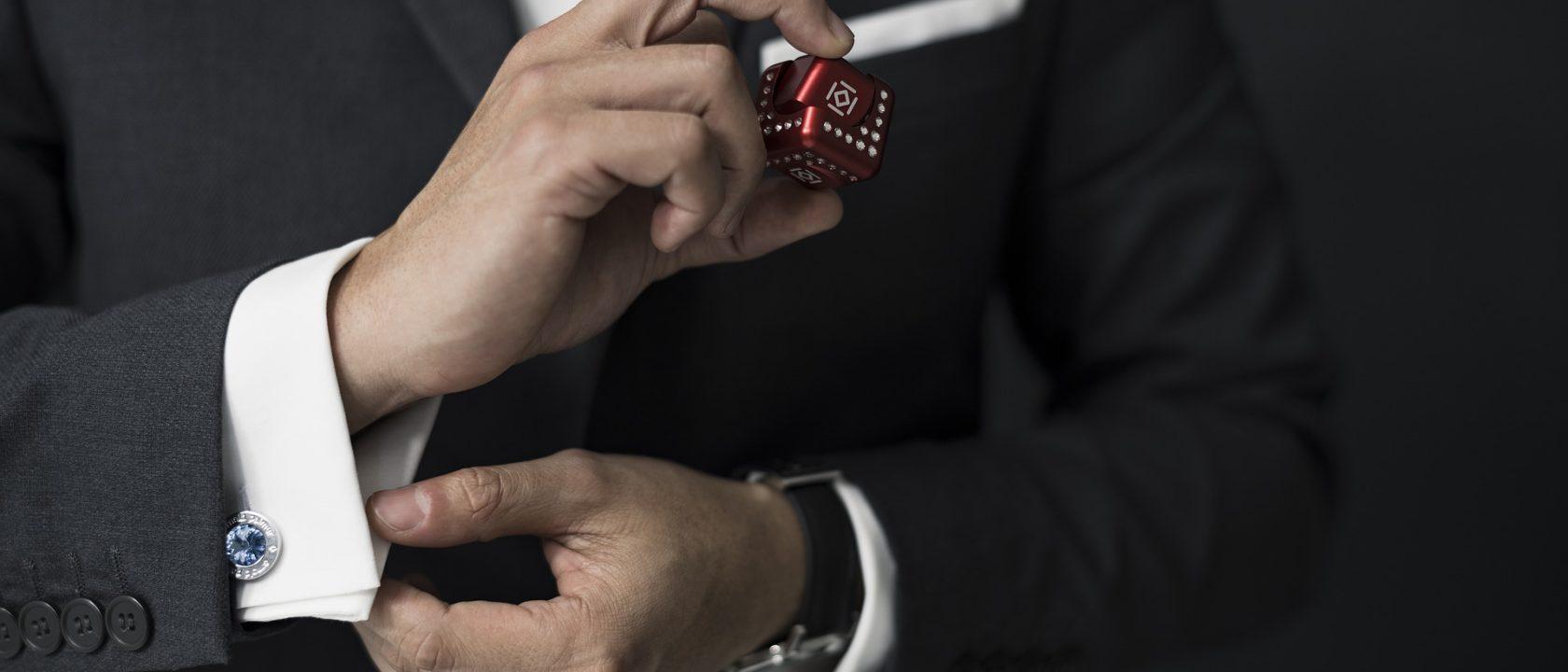 Takım elbisesinin kol düğmesini ayarlayan adam.