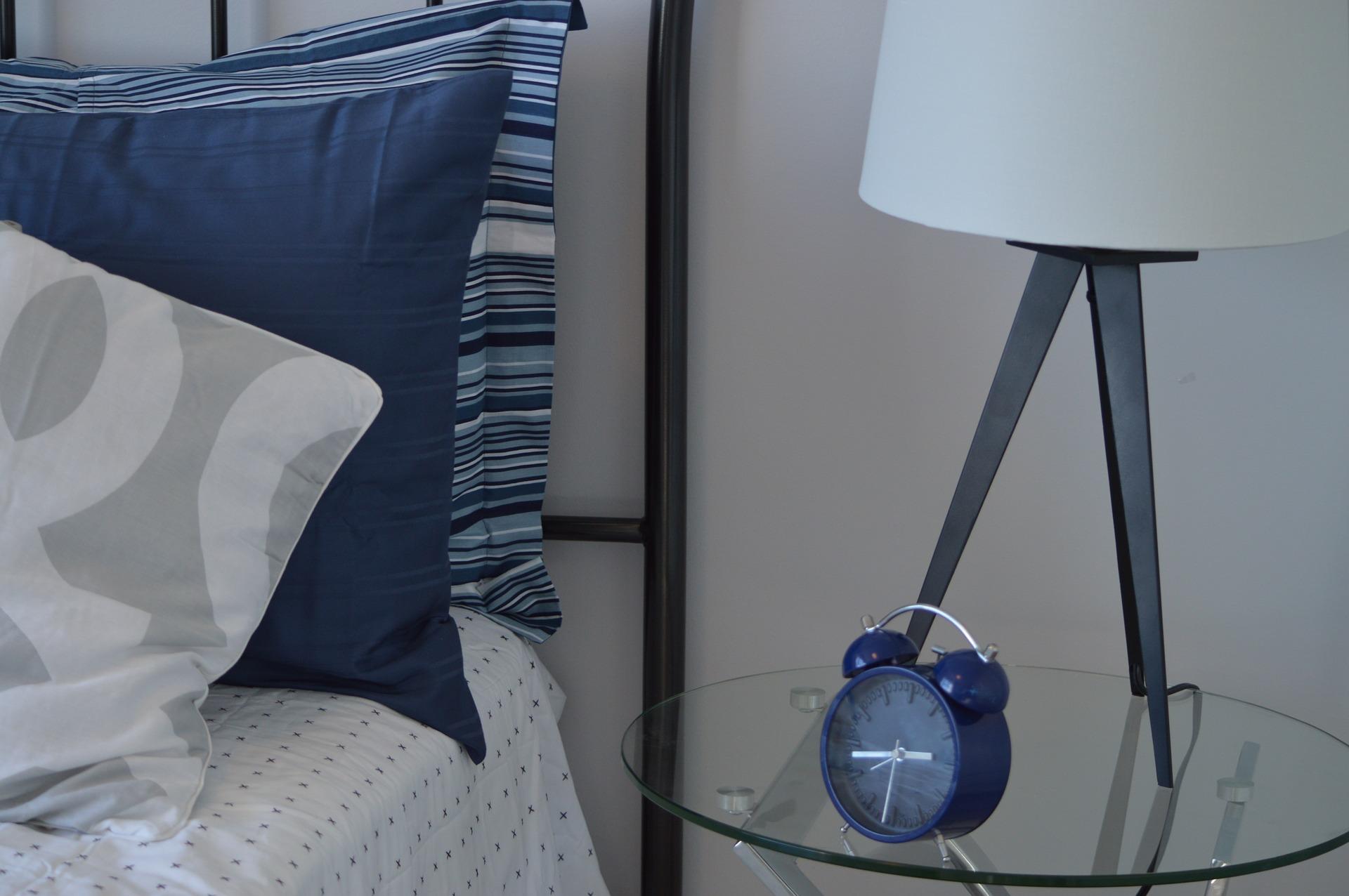 Yastıkların yanındaki cam sehpada duran mavi bir çalar saat.